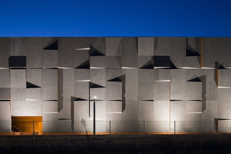 Slanted panels of precast concrete are positioned to catch the dawn and dusk sunlight that falls on the facades of this archival facility near the Australian capital, Canberra.