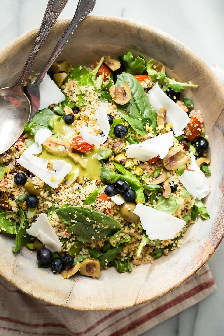 Fresh healthy couscous salad with greens, roasted tomatoes and goat cheese