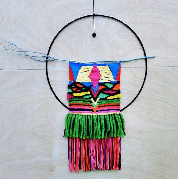 Tenture murale tissée haute en couleurs : bleu, jaune, rose, rouge, rose, orange, verte, noire. Le tissage ( 34X34 cm) se termine par de longues franges ( 36 cm). Il est fixé sur un bois de couleur gris bleuté. La tenture et son bois sont au centre dun grand cercle de métal (66 cm) recouvert de coton noir. Pour orner le cercle, une perle noire crochetée est suspendue. Cette tenture rehaussera de par ses couleurs vives un de vos murs intérieurs. Lensemble est entièrement fait main (tissage…