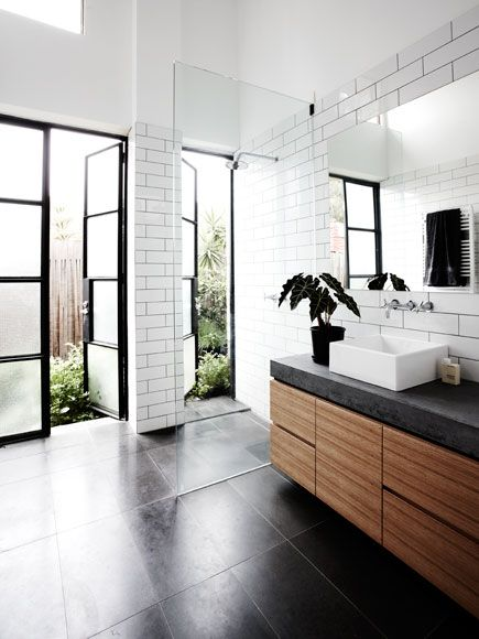 Modern bathroom with subway tile, wood modern vanity, black countertop black bathroom floors, steel frame doors