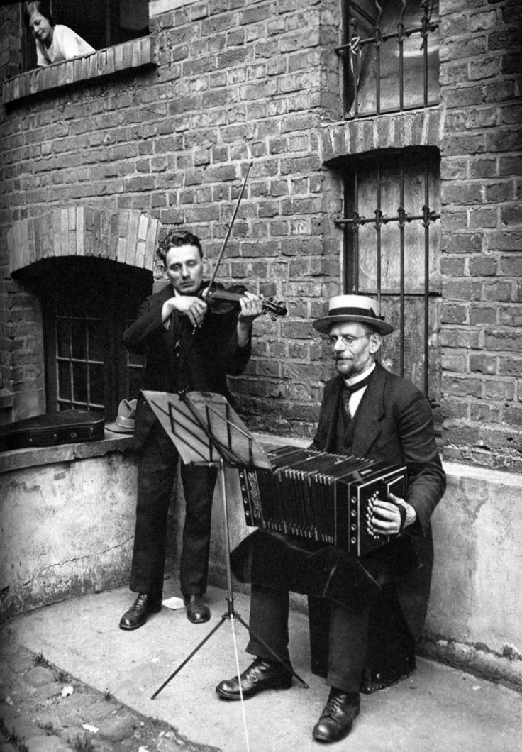 "August Sander: Courtyard Musicians, 1928 Exhibiting a staged formality, an accordionist and a fiddler ""perform"" in a courtyard while a young woman listens from a second-floor window. Sander's photograph condenses time by removing the accidental or spontaneous dimensions from the scene."