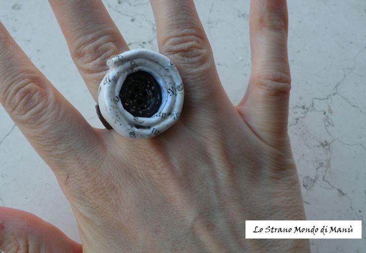 Riciclo creativo: anello realizzato con carta riciclata, una fascetta di cuoio, un bottone, smalto per unghie e brillantini.