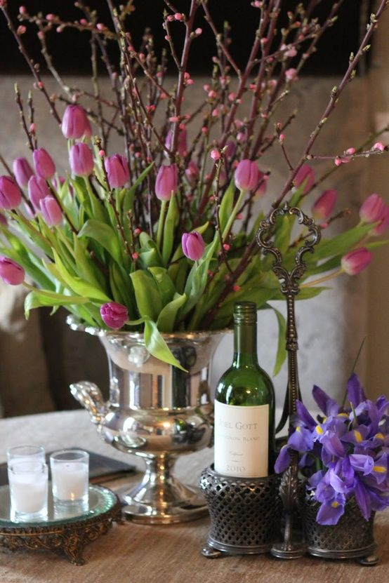 tulips & braches, plus all the textures around--silver champagne bucket, tarnished silver mirror tray, bottle caddy, and irises