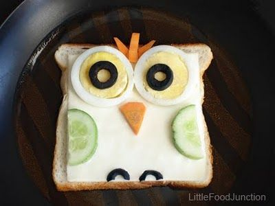 Owl Sandwich - brown bread topped with cheese, egg slices, olive , carrot, and cucumber .