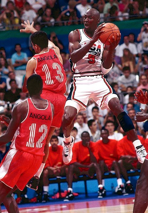 Michael Jordan---- contorts in air to get a shot off against Angola in Team USA's 1992 Summer Olympic matchup in Barcelona.The Dream Team crushed every team it faced,never winning by fewer than 32 points!!