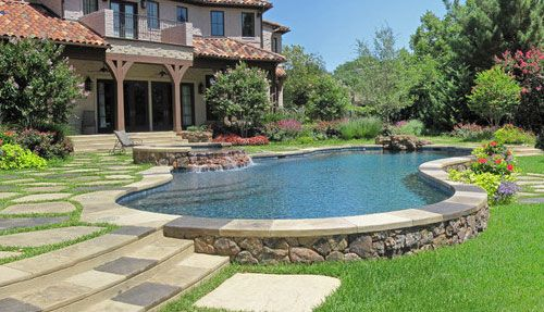 Free form pool with raised spa, rock veneer, boulder accents.