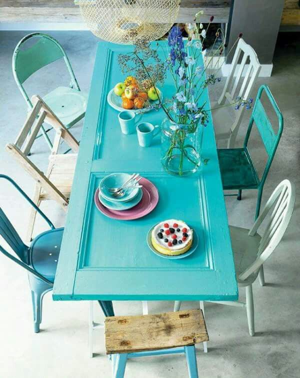 An old door, painted turquoise, used as a table! Love the eclectic look of this dining space. The mismatched chairs are perfect! A great idea for the patio.