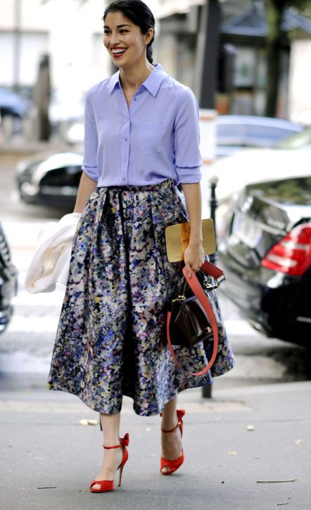 Caroline Issa in a floral skirt, blue button-down, and red heels