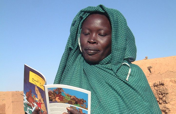 Bible Society is running literacy classes in Khartoum, Sudan.  A Nuba Moro woman in a refugee camp reading a Bible Society comic book.