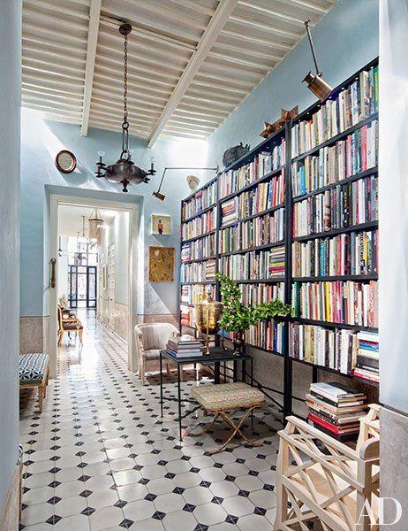 Iron bookshelves furnish the library of Robert Willson and David Serrano's Mexico home.  Pin it.