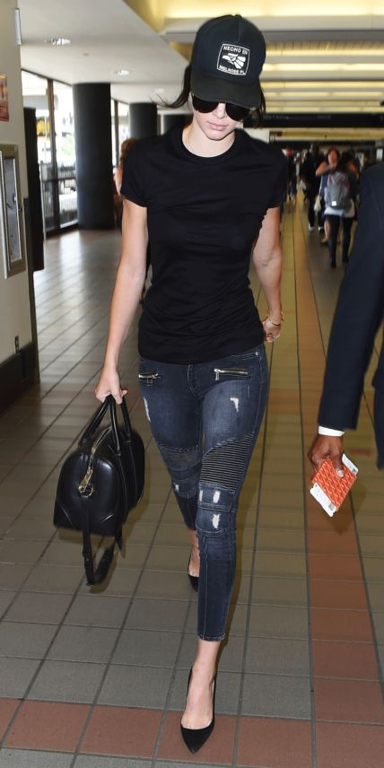 While dashing through LAX, the 19-year-old model showed us how to make a baseball cap look chic with moto jeans, a black tee, matching pumps, and a Givenchy duffel.
