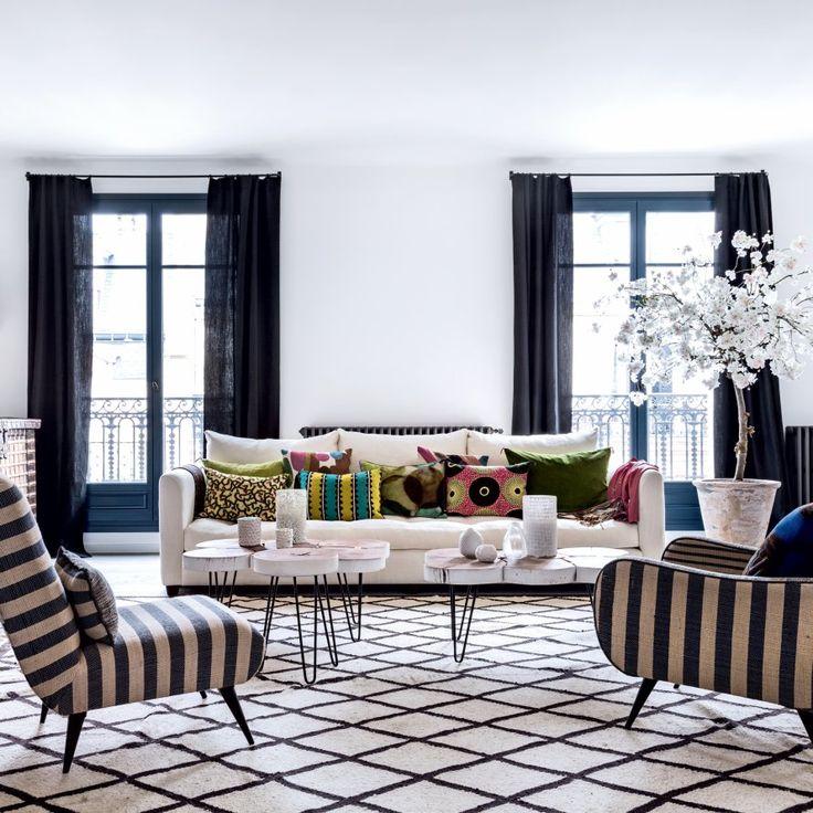 """<p style=""""text-align: justify;"""">Tapis berbère en laine, fauteuils """"Tabarka"""", (Rock the Kasbah). Canapé et coussins, Caravane. Tables basses Borgo delle Tovaglie. Arbre en..."""