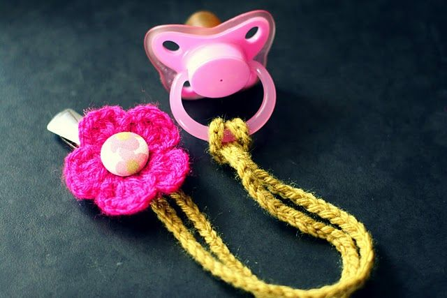 Pacifier holder. I made a couple of these so far. I crocheted a single strand and then left and opening and crocheted back down the strand to leave a loop to hook it onto the pacifier. And I used a button as the center of the flower. They turned out great!