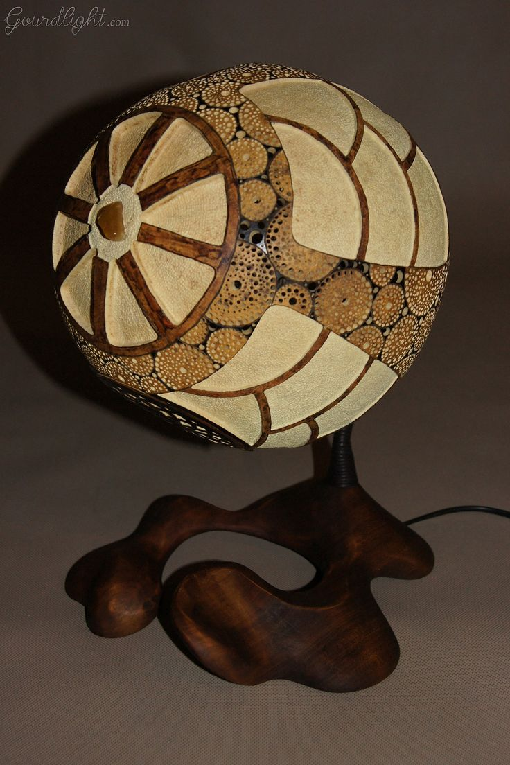 https://flic.kr/p/jDkBRE | Table lamp IX | Head of the lamp is made of Senegalese calabash. White parts are carved layer of the fruit which change the color to red/orange when the lamp is switched on. On the bottom of the lamp there's perforated closing part locked by magnets. The lamp was painted with wood oil and alcohol ink. Black parts are burnt calabash surface. The center element is genuine Baltic amber- ranked as the world's finest;  resin from the ancient trees dating back ~40…