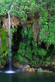 Krause Springs in Spicewood is possibly the most beautiful swimming hole in the state. It is just under an hour's drive northeast of Fredericksburg and 45 miles west of Austin. Situated on a bluff overlooking Cypress Creek, Krause Springs is actually two swimming holes in one. As the rolling ranch land begins its rapid descent to the creek and Lake Travis, the Krause home sits at a high point with the parking lot. The next level below houses the spring-fed swimming pool and below that is the…