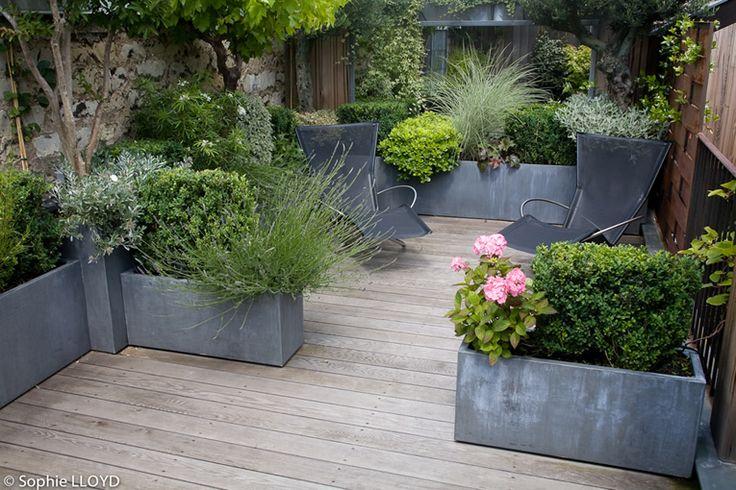 Petite terrasse en bois avec ses jardinières en métal.