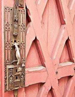 Light pink / coral door with ornate brass door knob