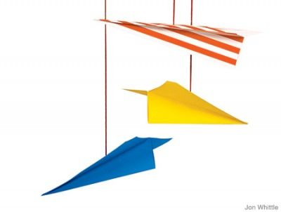 Hang paper airplanes made from colored paper and yarn from the ceiling for a modern mobile effect