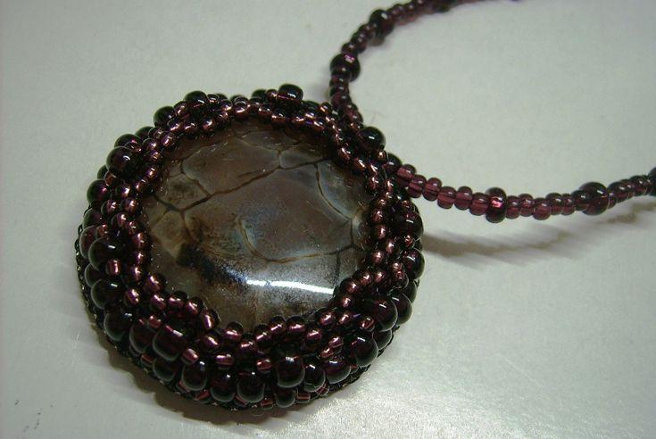 Ny-562. Barna színű, ásvány kő medálos nyaklánc, lila színű üveg gyöngyökkel. A nyaklánc hossza: 42 cm. Kapcsolója bronz színű delfin kapocs. A medál mérete: 39mm. Ára: 990.-Ft.