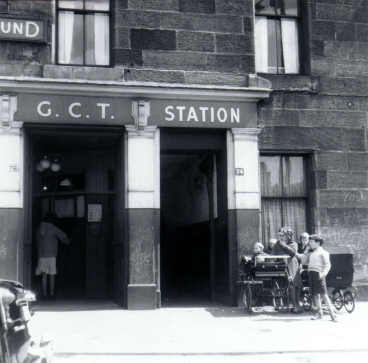 Children with prams at the entrance to Kelvinbridge station on the Glasgow Underground, 1962. A woman is standing at the ticket booth. The entrance was located in a tenement building next to the Great Western Bridge facing west on to the Caledonian Railway Co's Kelvinbridge Station and goods yard, and the River Kelvin beyond. Reproduced with the permission of Glasgow City Council, Glasgow Museums - TheGlasgowStory