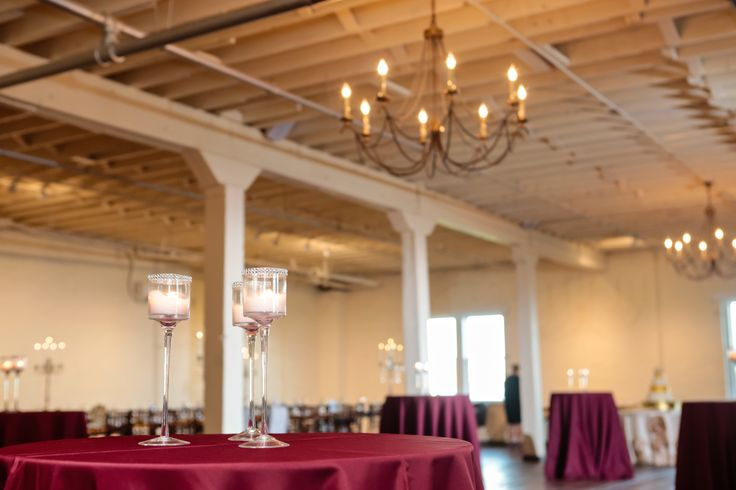 BRIK Venue | Fort Worth Wedding | Industrial | Warehouse | Texas | Fairy Tale Photography | Reception | Table Decor | Wooden Tables | Cocktail Tables | Maroon Tablecloths | Candles | Cocktail Hour | Chandelier | Wood Floors