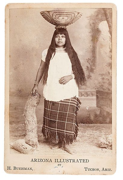 Henry Buehman Cabinet Card of a Pima Woman. Young Pima woman balancing a woven basket on her head, with H. Buehman's Tucson, Arizona imprint on recto.