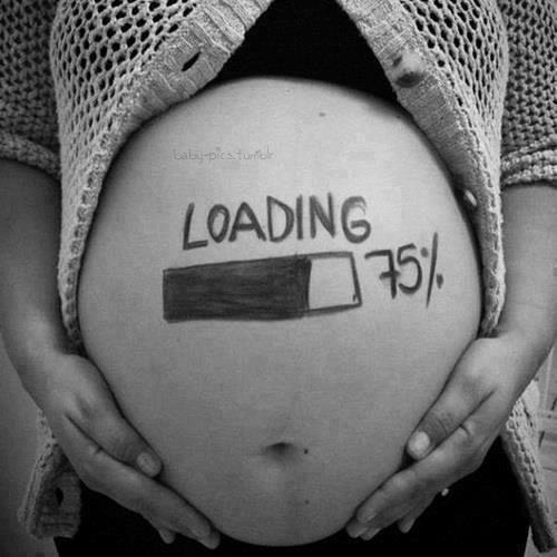 Femme enceinte avec inscription 75% loading sur le ventre rond