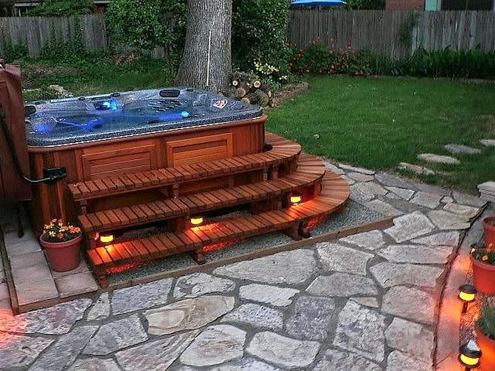 Here is another wooden hot tub or spa which presents a grand and rich look. It is amazing and perfect for an evening plunge. The tub has been placed on the stone patio platform surrounded with green grass, flowery bushes and trees. The unique and romantic effect has been achieved by giving the wooden tub some amazing light effect under the steps.