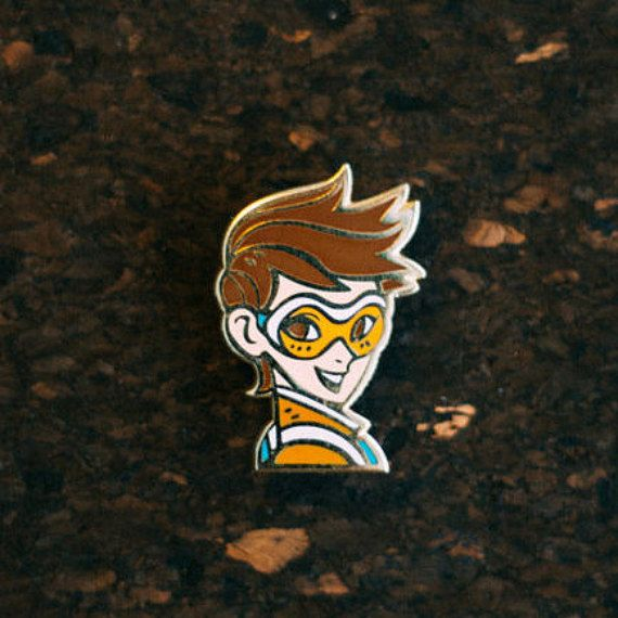 Overwatch Fan Art Hard Enamel Pin by Lunarite.  Tracer is casted on a 24k gold plated zinc alloy with a hard enamel process to achieve a very polished look. All pins are pinned with a butterfly clasp firmly inside a 5cm W x 5 cm L x 3.5cm H sturdy black cardboard box with inner cushion padding. Each pin is has its own box to withstand the shipping process.   DETAILS: Dimensions: 23mm width x 34mm height Material: Zinc Alloy Process: Hard Enamel Plating: 24k gold Clasp: Gold Metal Butterfly…