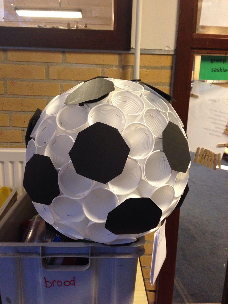 Voetbal surprise Nodig: ongeveer 100-150 bekertjes van 150cc. Verkrijgbaar bij makro of Sligro. De standaard 180cc is te groot, krijg je een giga bal. Niet ze strak aan elkaar, de ronding ontstaat vanzelf. Stop je kado erin. Prop crepepapier met lijm in een bekertje en plak de zwarte 8-hoeken erop.