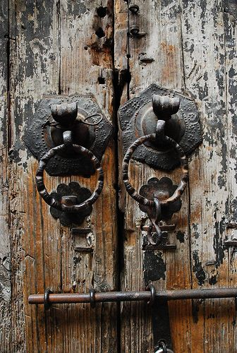 Gorgeous iron pulls and perfectly weathered wood door....