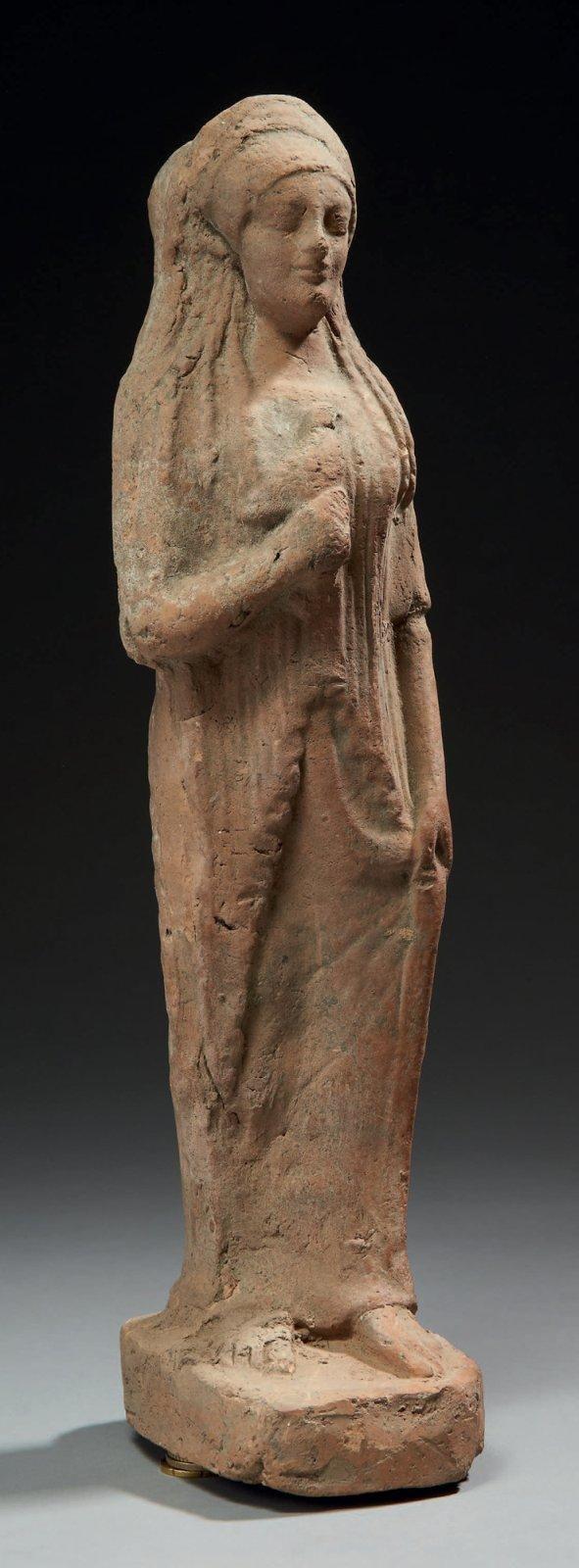 KORÉ À LA COLOMBE. Grande statuette représentant une koré debout sur une base. Elle est vêtue d'un long chiton couvert d'un himation plissé dont elle saisit un pan de la main gauche; de la main droite, elle tient une colombe à hauteur de la poitrine. Sa coiffure, formée de longues parotides, est ceinte d'un polos. Terre cuite orangée. Art Grec, fin du VIe siècle av. J.-C.