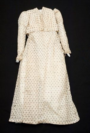 An early 19th century (1825) cream muslin dress with woven check of thicker warp and weft threads. Block printed in purple (now changed to brown), with all-over spot design of star-like flowers. National Trust. Nancy Bradfield p118