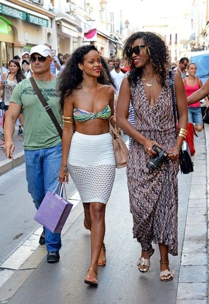 Rihanna wears a tiny bandeau top and a white mesh skirt as she makes her way through a crowd of fans while on vacation in the French Riviera.