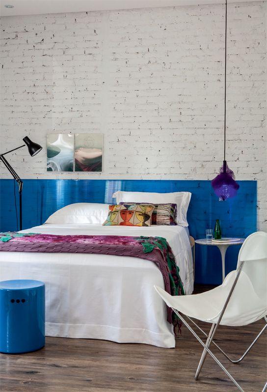 Algumas paredes foram descascadas, revelando a textura dos tijolos. No quarto, eles receberem esta pintura off-white. A moldura azul valoriza a roupa de cama (Trousseau). Luminária e almofadas da Conceito Firma Casa. Cadeira da Futon Company, banqueta da Clami e quadros da Arterix.