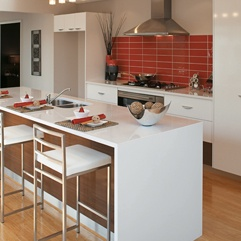 Red subway tile splashback with white cabinetry Via Crosby Tiles
