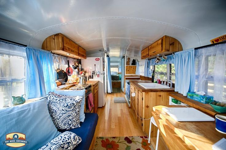 The white, blue and natural wood make this bus conversion home look light and airy. I love the cabinets that curve along the ceiling - great use of space.