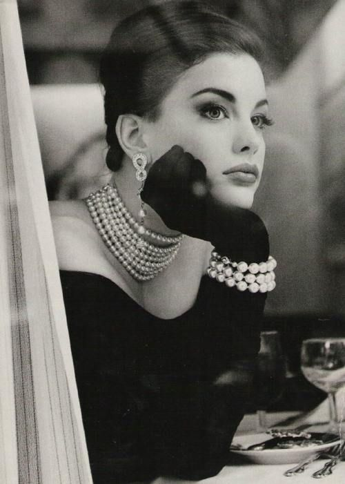 A very elegant duo with black satin gloves and dazzling white pearls.