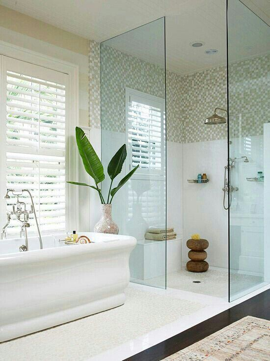 Free Standing Tub with Elegant Silhouette | All Glass Shower | White Tile in Bathroom | Window with Shutters over Bath tub