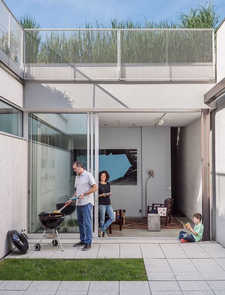 """The home's enclosed courtyard sits at """"the heart of the structure,"""" says Baumann, who resides with his wife, Lisa Sardinas, and eight-year-old son, Oskar. """"This is clearly the dominant space; everything flexes towards it."""" Baumann cast the square concrete floor tiles himself, enlisting the help of his son. A small, neat patch of grass—a playful nod to the archetypal domestic lawn—is edited down to a charming folly."""