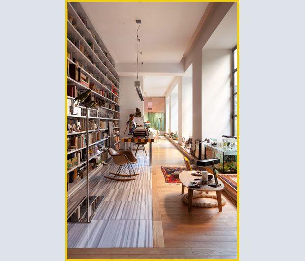 Davanti alla libreria, la Rocking Armchair di Charles & Ray Eames per VITRA . Il tavolo con il piano a scacchi è un progetto di Italo Rota. Sul parquet originale, un inserto in marmo tagliato a linee verticali.