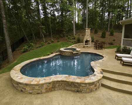 Simple but eloquent Swimming Pool. Irregular Flagstone and Stamped concrete with an upper deck area with Fireplace
