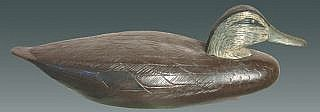 Realized Price:  $3,500 Outstanding black duck circa 1900 from the Stratford school of carving, Stratford, CT. Hollow carved and extremely light with a thin, applied bottom board. Notably pinched breast, shallow ice groove and lightly carved wingtips on the tail. Carved and stamped individual feather detail. Closely aligned incised lines cover the upper three quarters of the back and body as well as covering the entire head