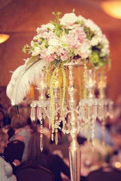 30 Ideas for Centerpieces  Wedding Reception Photos on WeddingWire.  Chandelier center piece with feathers and flowers! So modern and vintage at the same time.