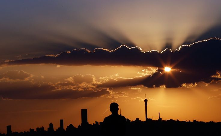 A man watches the sun set over the skyline of Johannesburg, South Africa