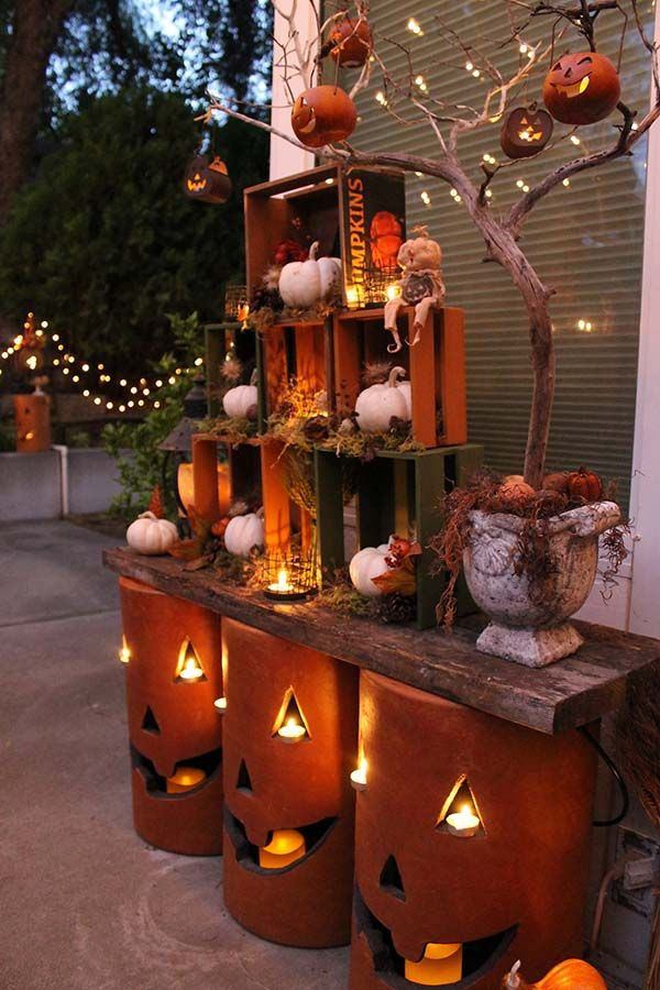 cozy fall patio decorating ideas. Nested crates and pottery pumpkins with LED candles and string lights would make your outdoor area shine!