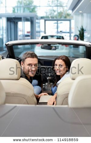 Young couple in a cabriolet in the showroom - stock photo