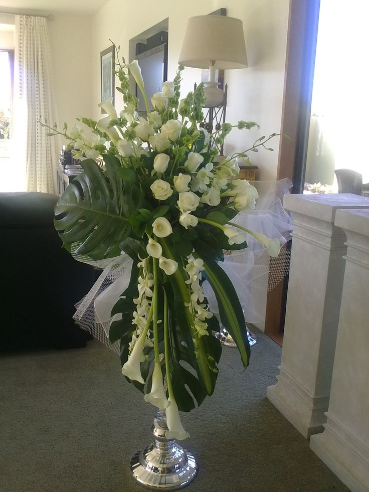 Tall and elegant this combinations of roses, callas, monsteria for the church alter.