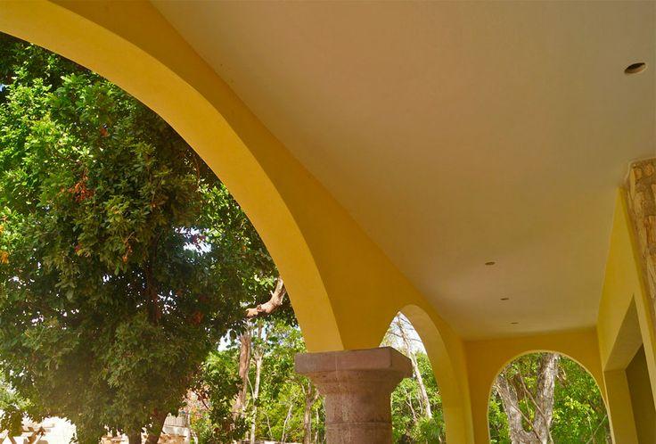 Arches and stone columns of the private terrace. Hacienda del Río Custom Homes model home. Playa del Carmen real estate area.