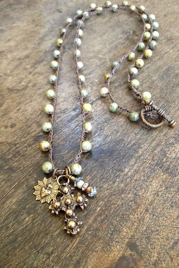 This boho chic necklace features gorgeous opaque luster Czech beads crocheted onto nylon cord featuring an artisan bronze cross pendant and